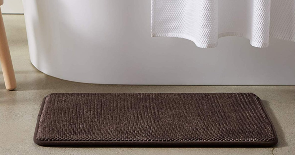 brown bath mat on floor in front of bathtub