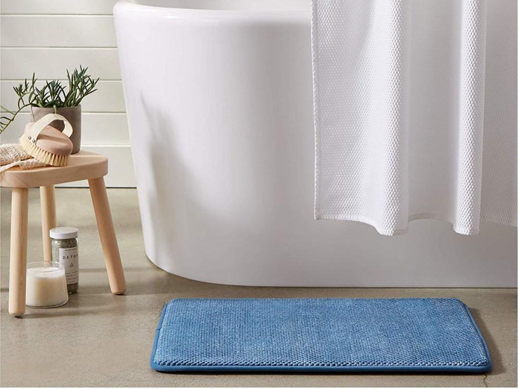 blue bath mat in front of floor by bathtub