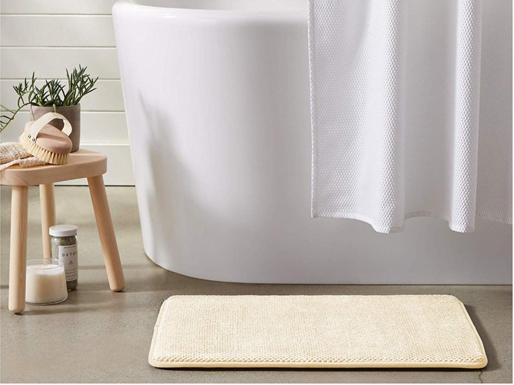beige bath mat on floor in front of bathtub