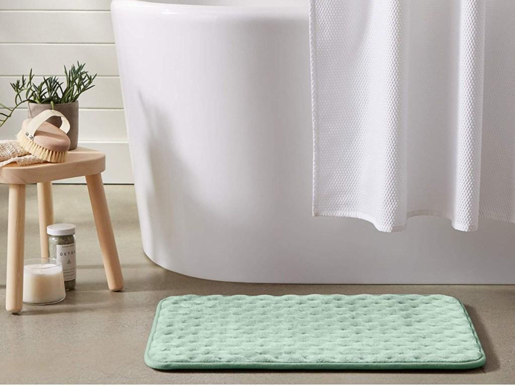 green bath mat on floor in front of bathtub