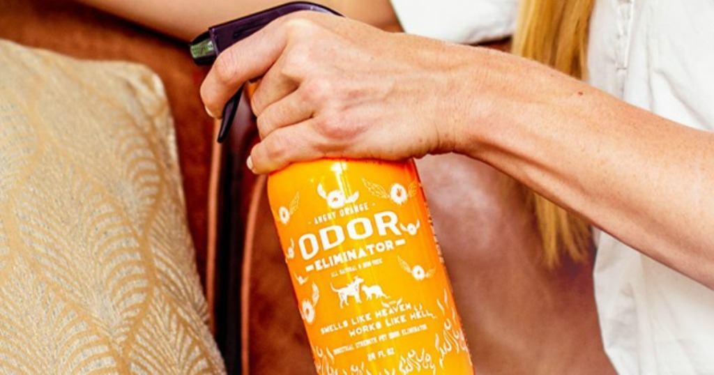 lady holding a bottle of Angry Orange odor eliminator