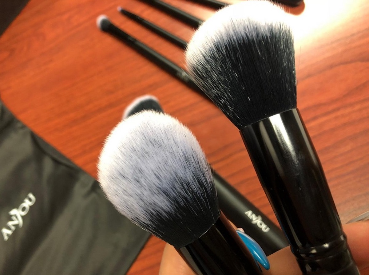 Person holding 2 Anjou Makeup Brushes