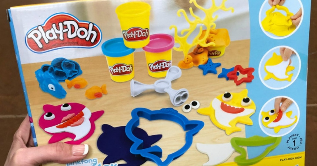 hand holding up baby shark play doh set box