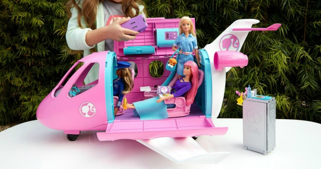 Child playing with a Barbie plane with accessories on a table, outside