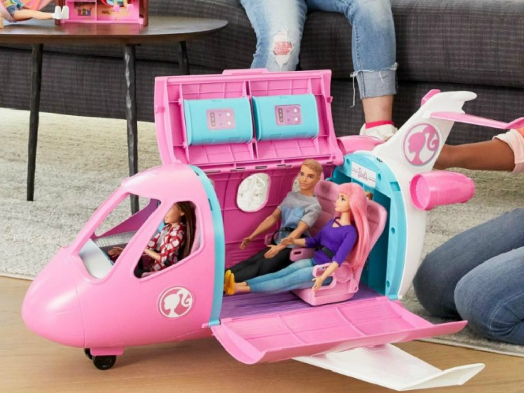 Girls in living room playing with Barbies and Barbie playsets