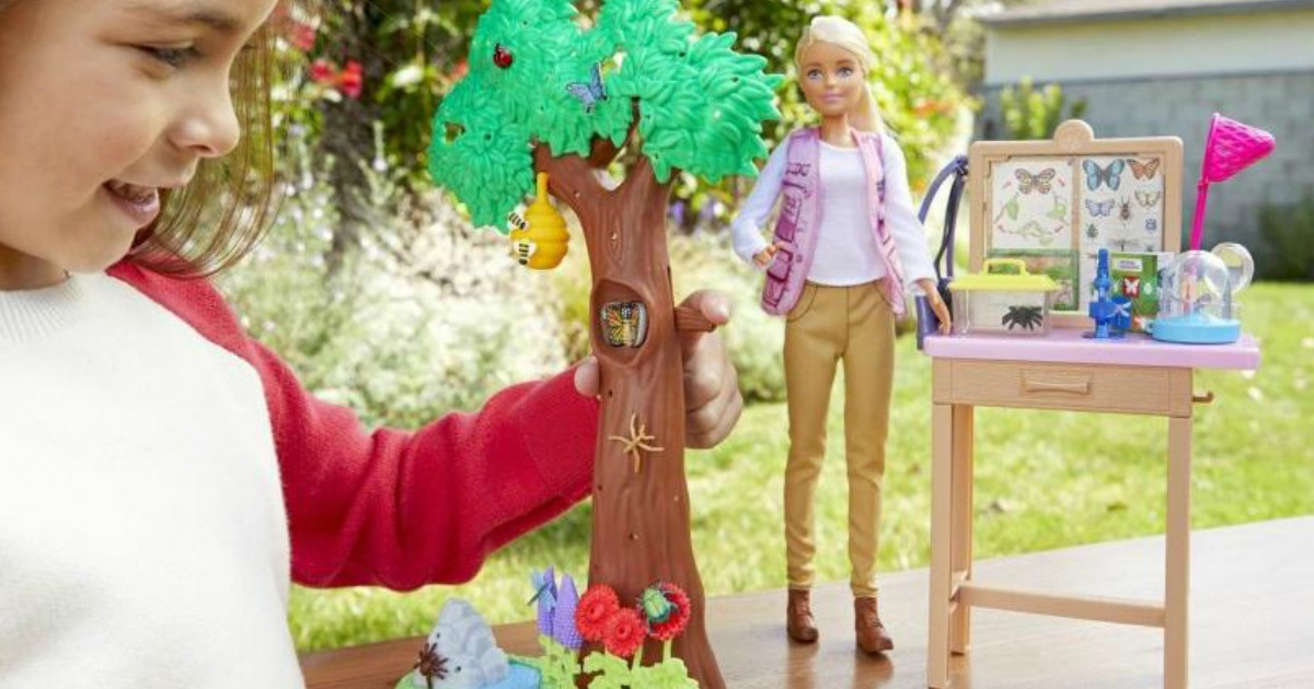Girl playing with a Barbie Entomologist Doll & Playset outside