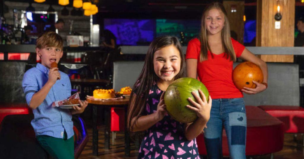 Kids holding bowling balls at bowling ball