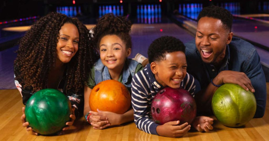Family laughing and holding bowling balls