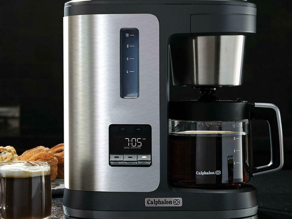 coffee maker with coffee cup beside it