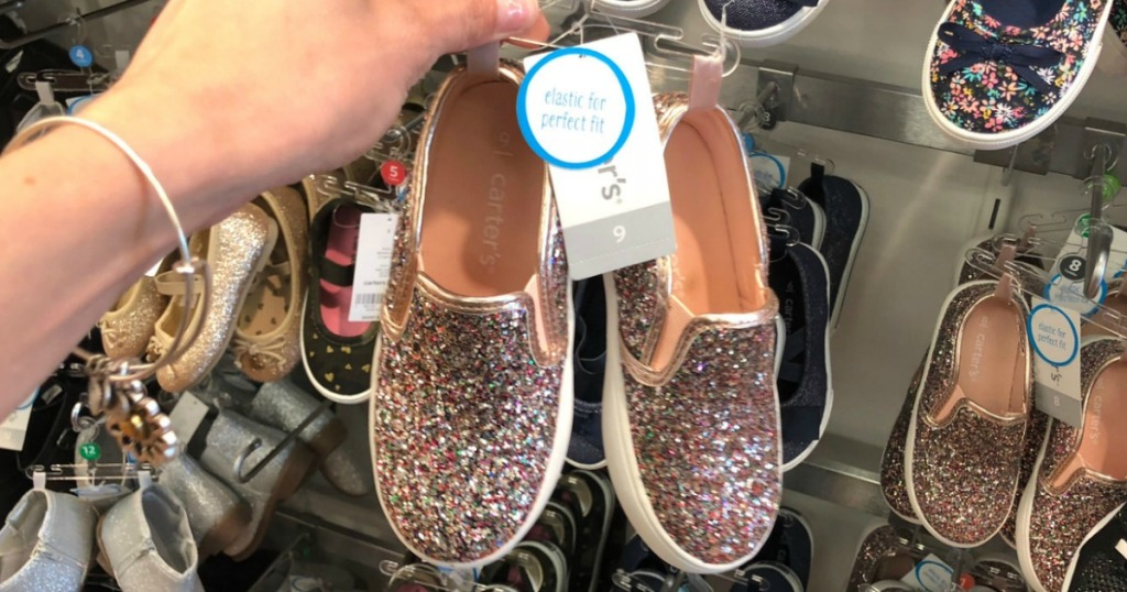 Pink glittery slip on shoes for toddler girls on hanger in hand in-store