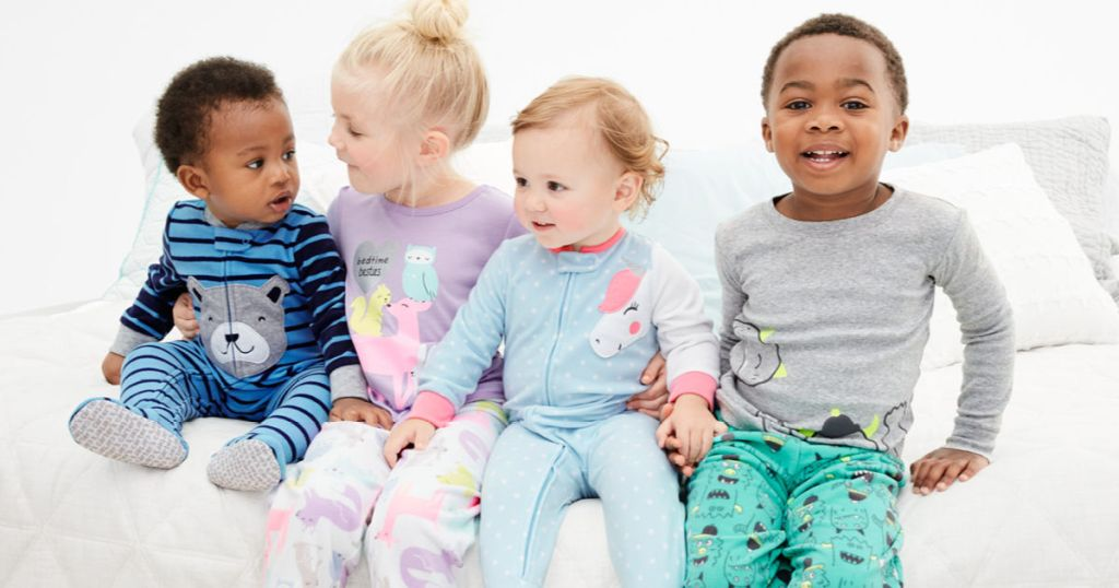 babies and children sitting on bed in carter's pajamas