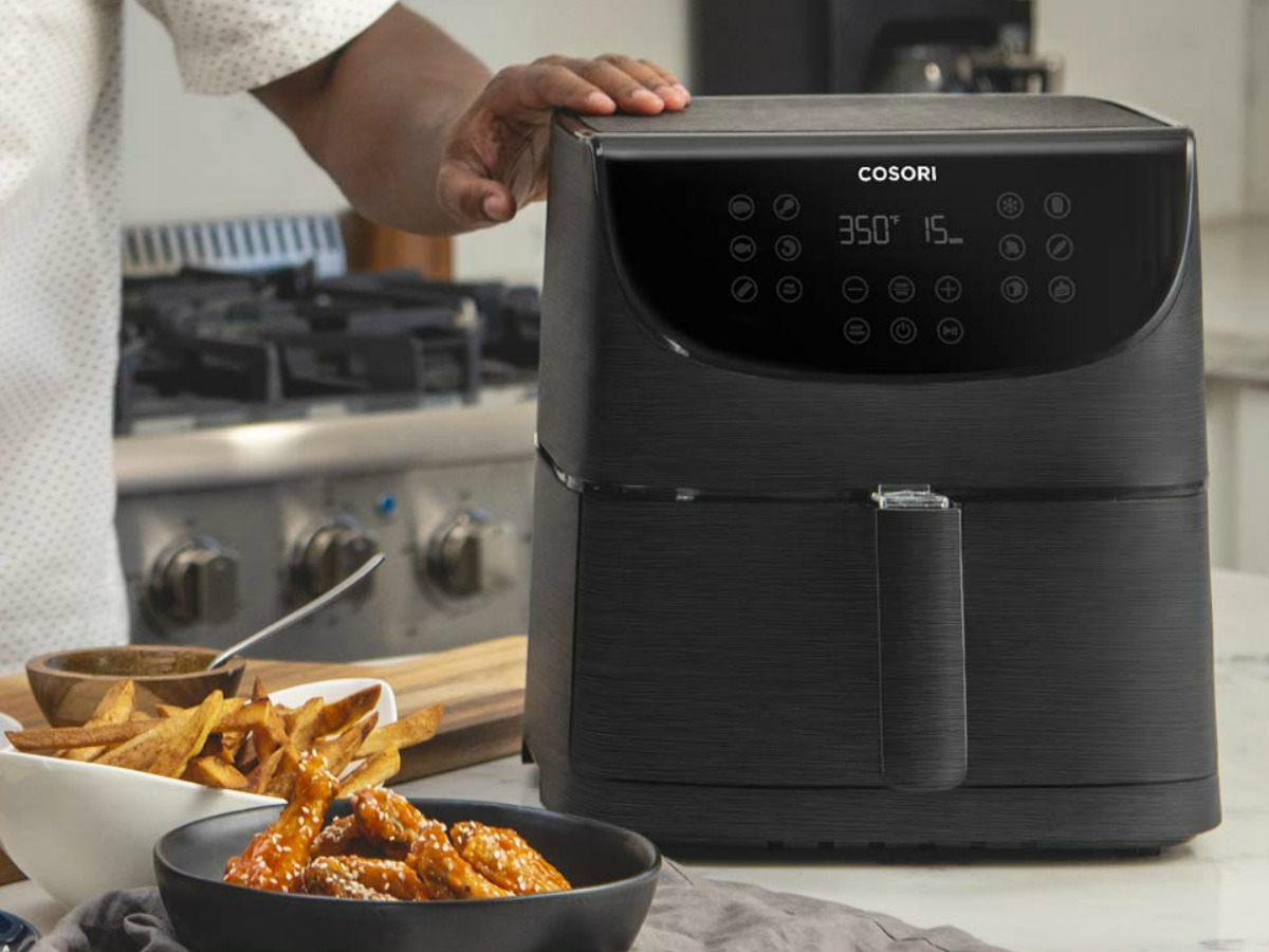 Amazon Corsori Air Fryer in black on counter in kitchen near air fried foods