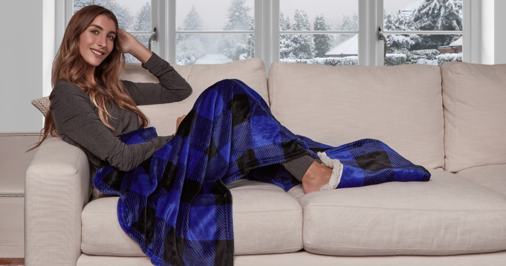woman using cuddle duds throw on couch