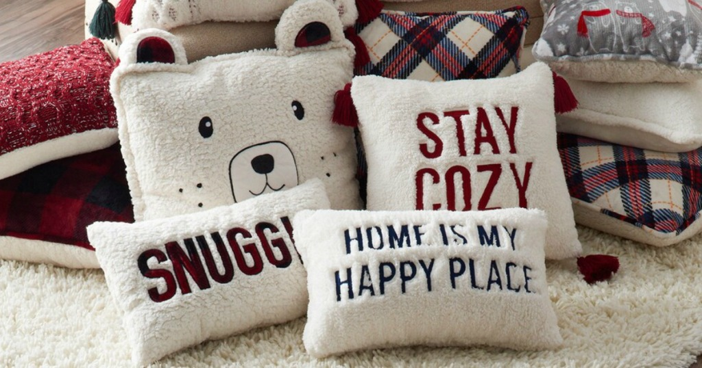 Cuddl Duds Holiday Throw Pillows stacked on carpeted floor
