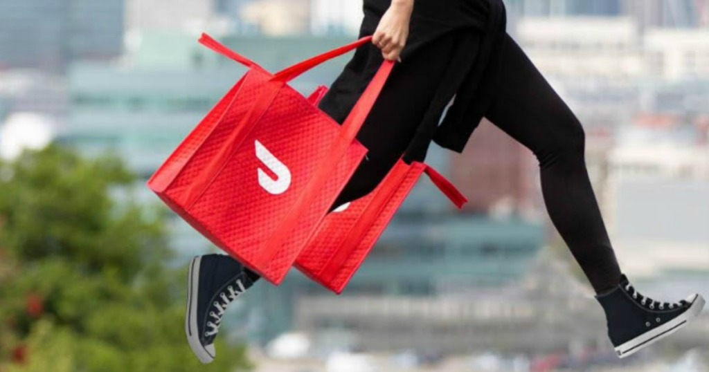 Woman carrying two DoorDash delivery bags