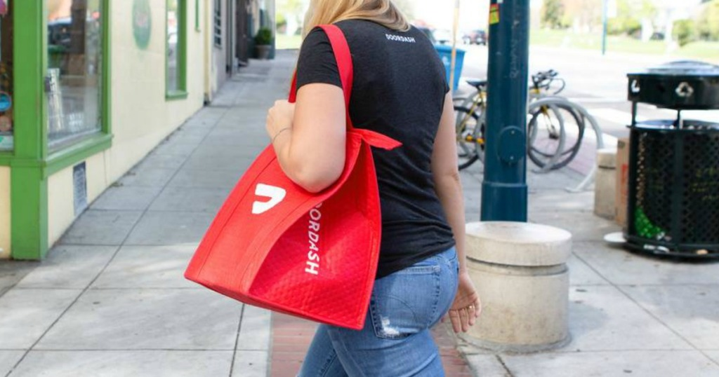 Woman delivering food with DoorDash delivery bag