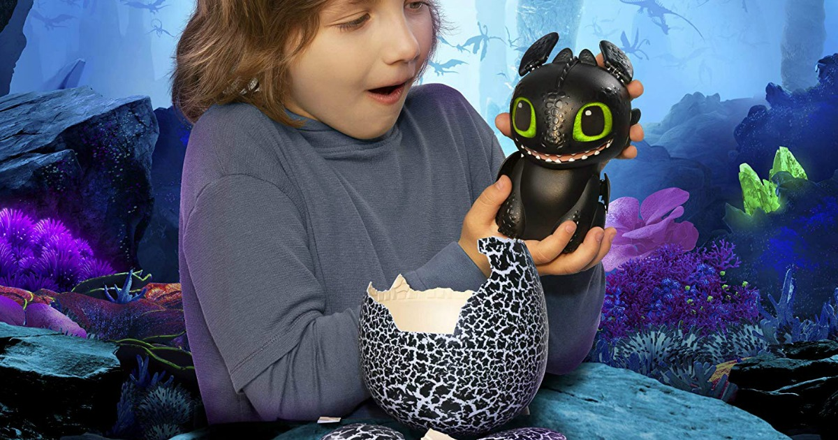 boy playing with interactive toothless hatching dragon