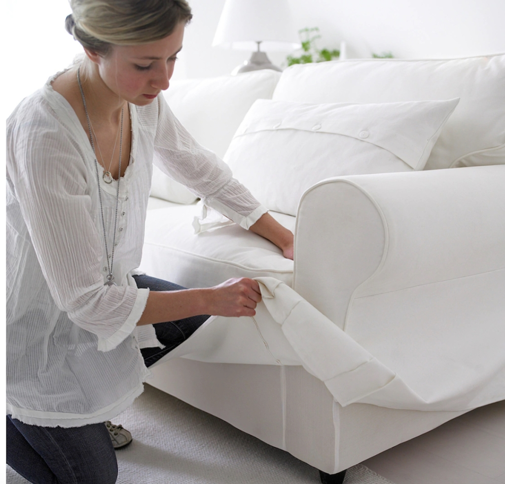woman changing white slipcover on sofa