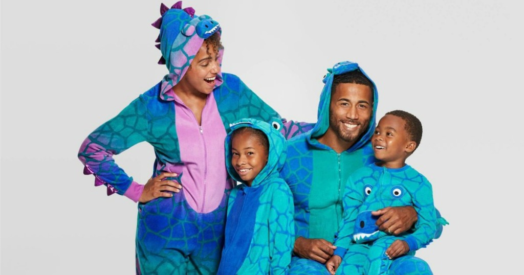 family wearing matching dinosaur union suits
