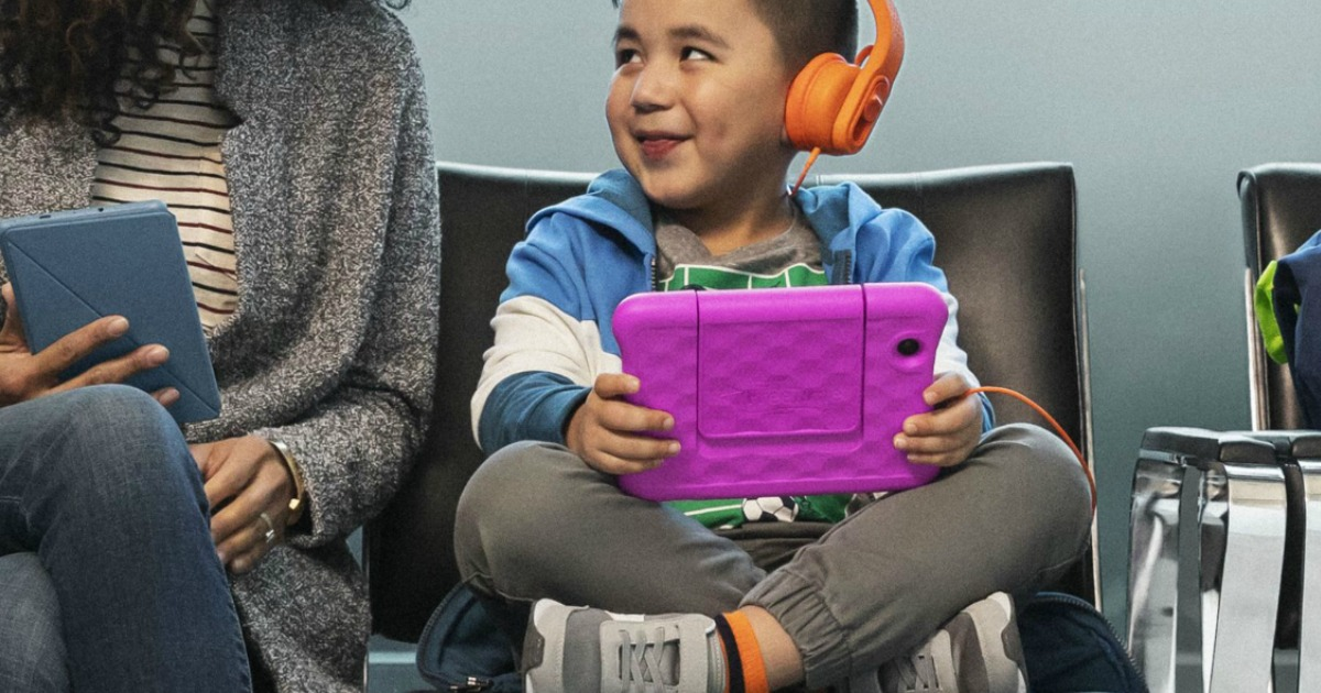 Kid sitting next to mom with Fire Tablet, wearing orange headphones
