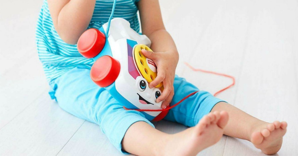 little girl on floor playing with Fisher-Price Chatter Telephone