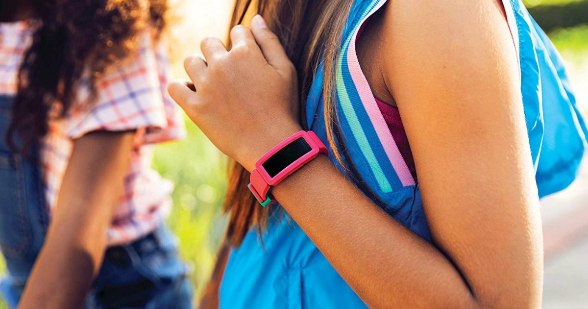 Girl wearing a pink kids activity tracker and backpack
