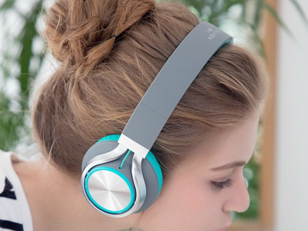 Girl wearing silver and teal headphones