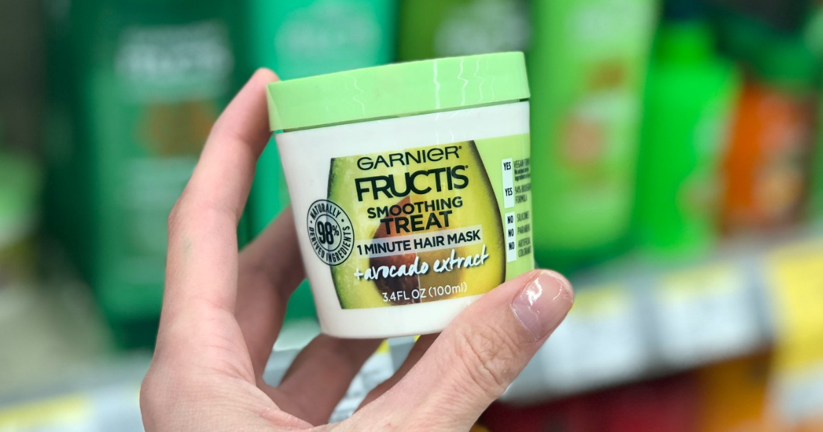 hand holding up a Garnier Hair Mask cup in front of a store shelf