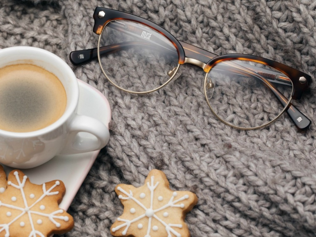 Pair of cat eye glasses on knitted surface with holiday sugar cookies and coffee