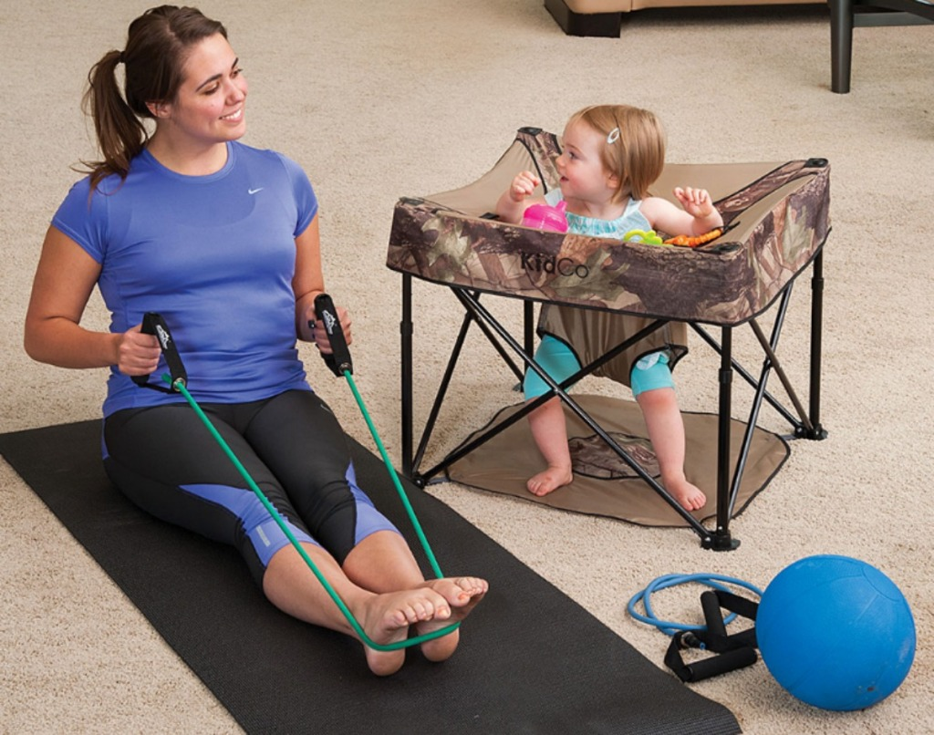 woman stretching on a yoga mat near a toddler girsl in a GoPod activity center