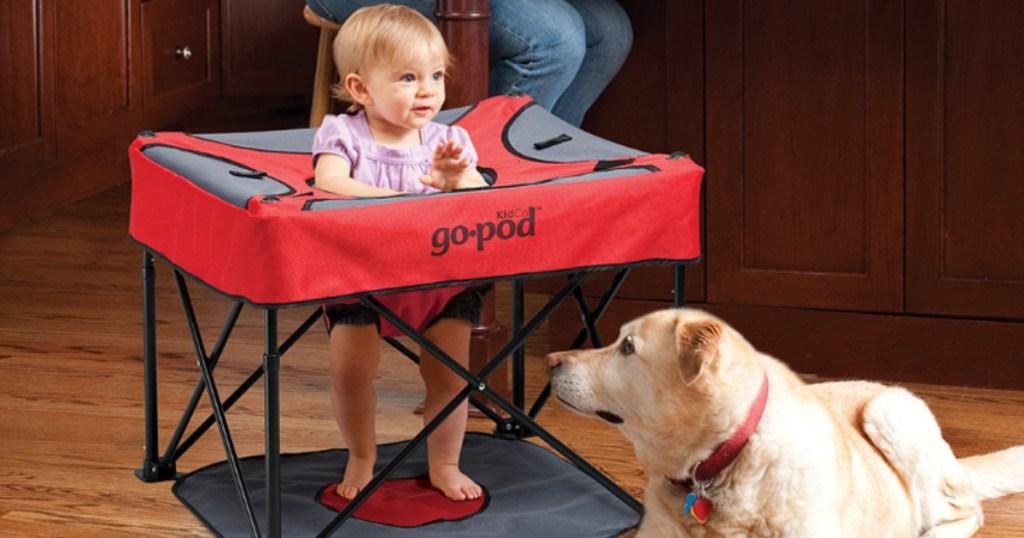 toddler girls sitting in GoPod activity center near a dog