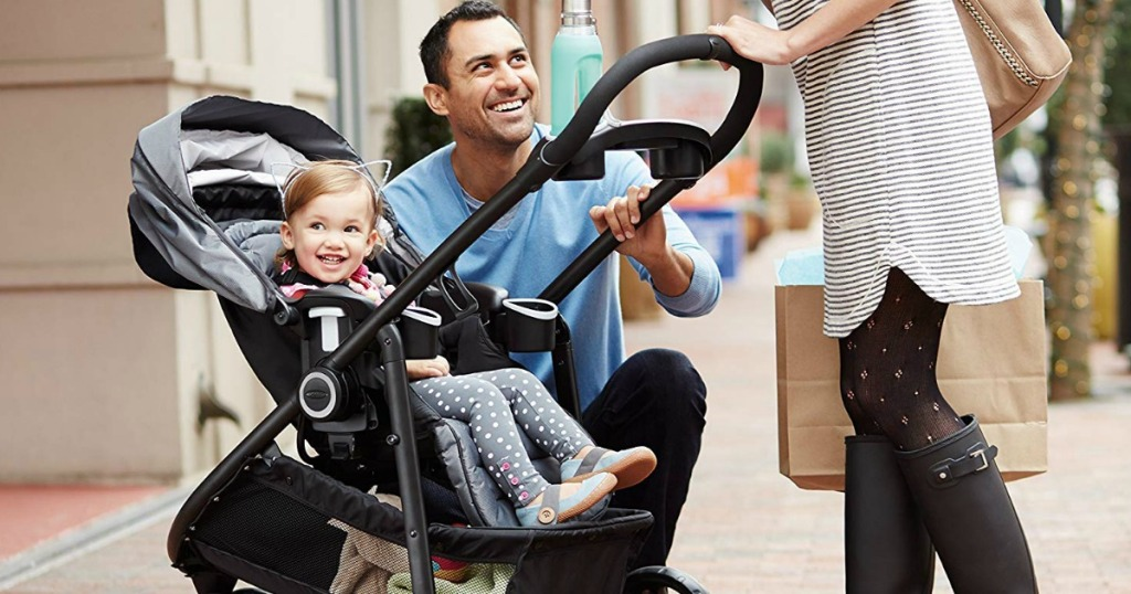 man standing by kid in stroller