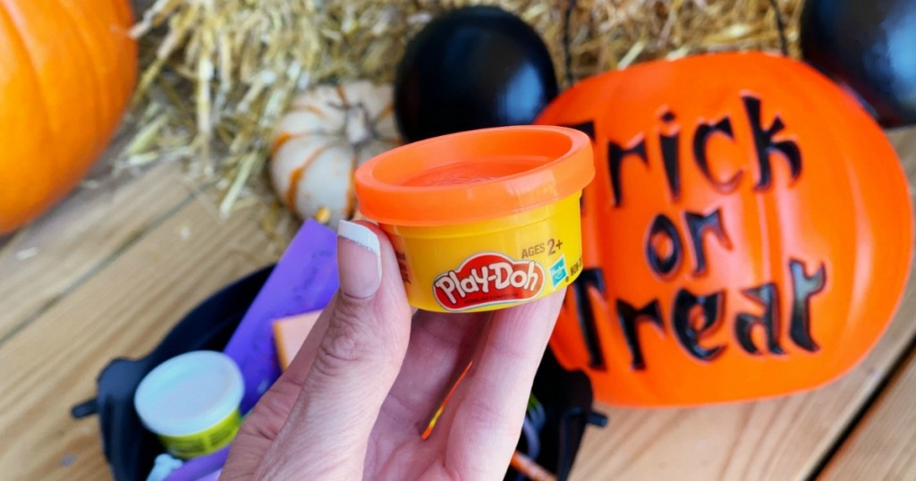 woman holding Halloween Play-Doh mini can next to Halloween decor
