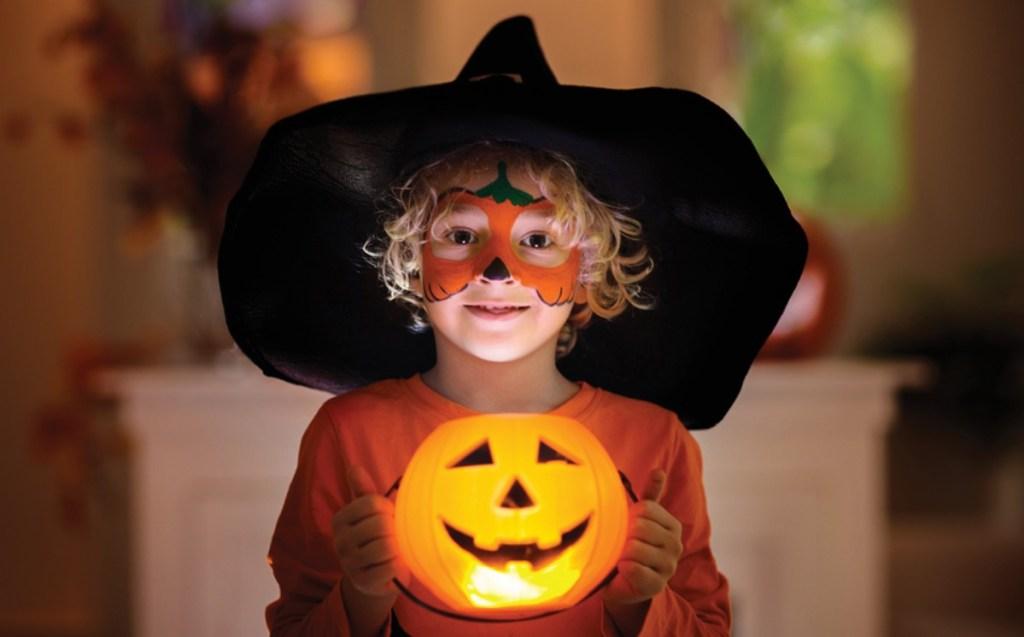 boy wearing witch costume holding pumpkin