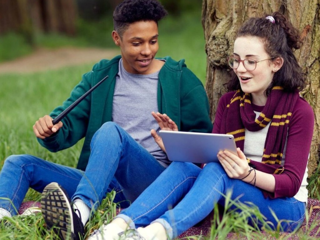 Two teens using the Harry Potter Coding program outside on a tablet with the wand