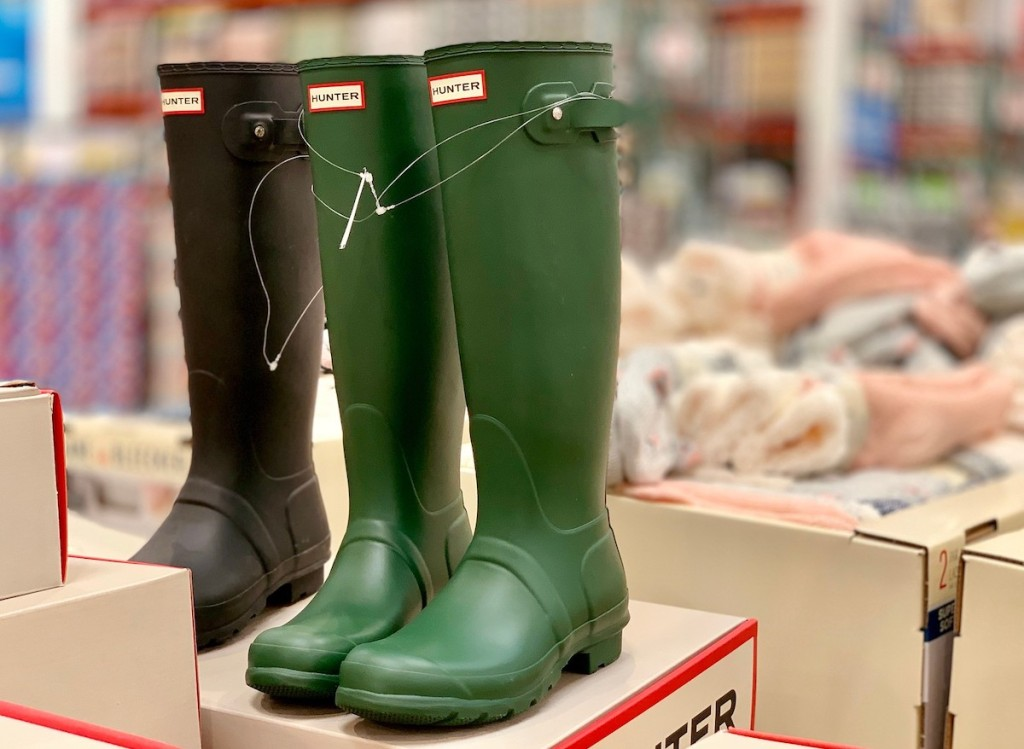 green and black hunter boots sitting on top of shoe boxes