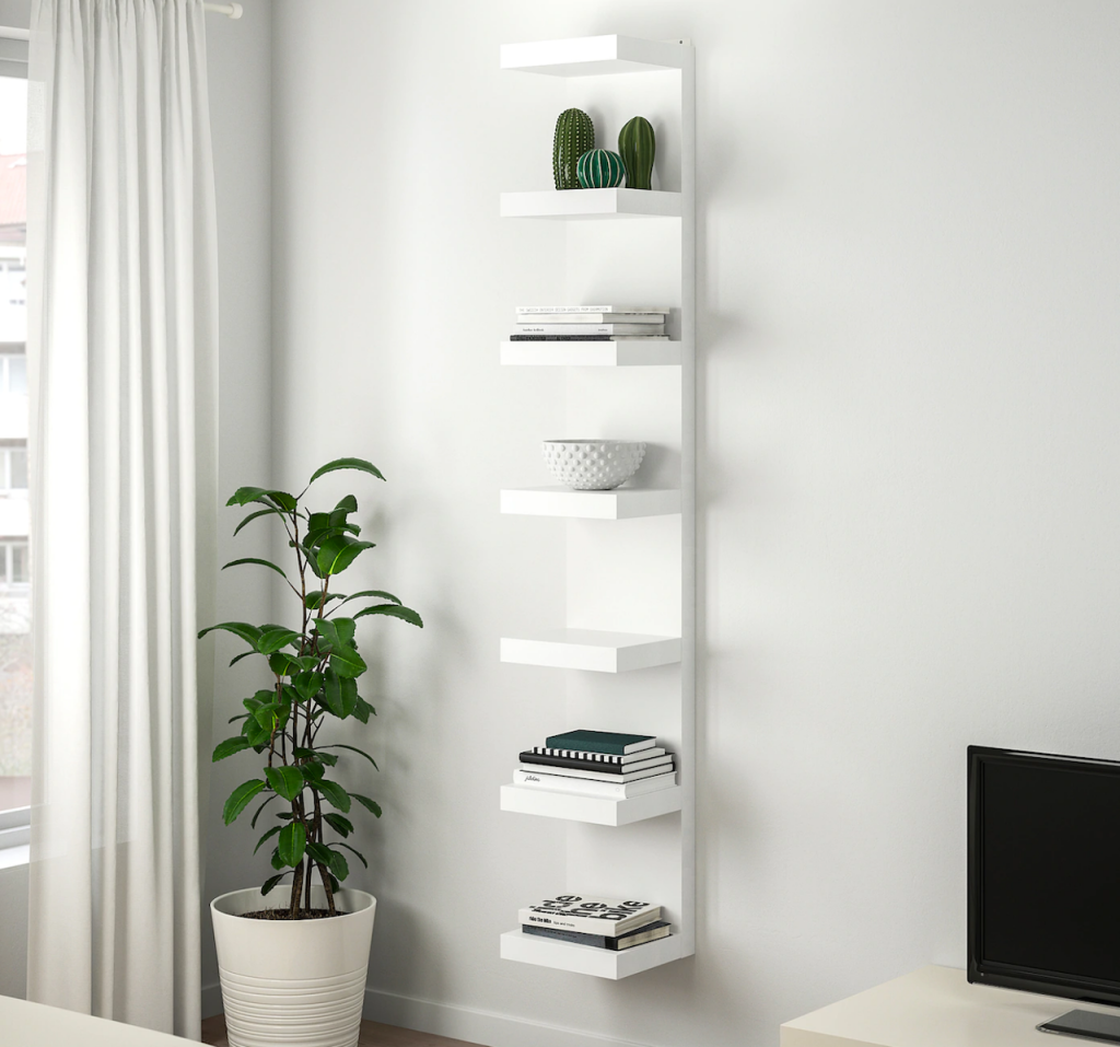 IKEA white wall unit with books and plant next to it