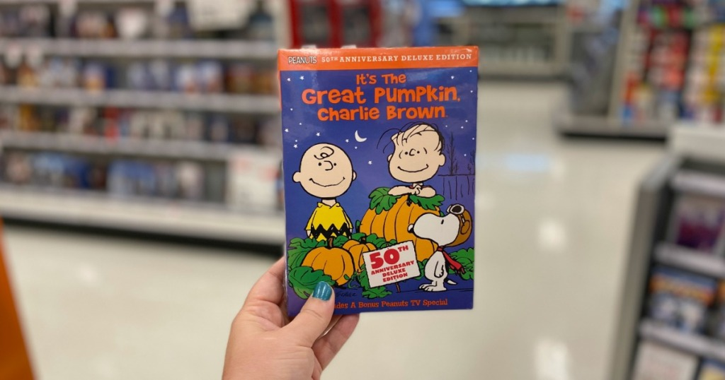 woman holding It's the Great Pumpkin, Charlie Brown 50th Anniversary Edition DVD at Target