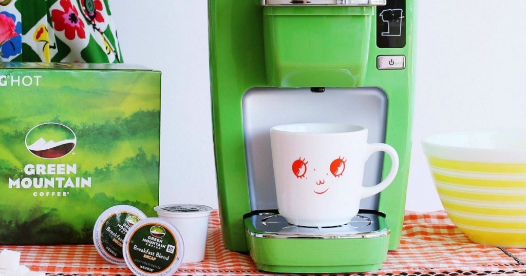 Green kcup brewer on counter near kcups and bowl