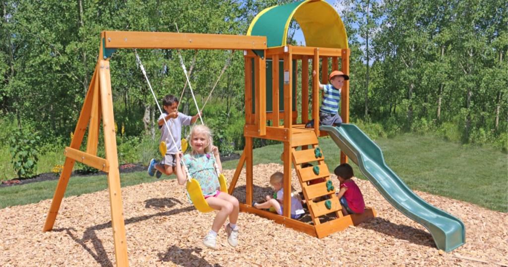 kids playing on kidkraft wooden swingset