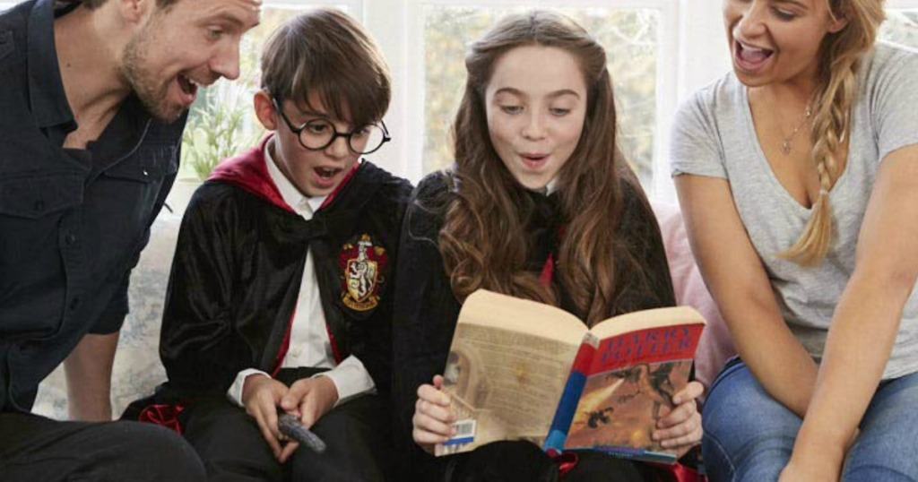 Kids wearing Harry Potter costumes and reading a Harry Potter book with their parents