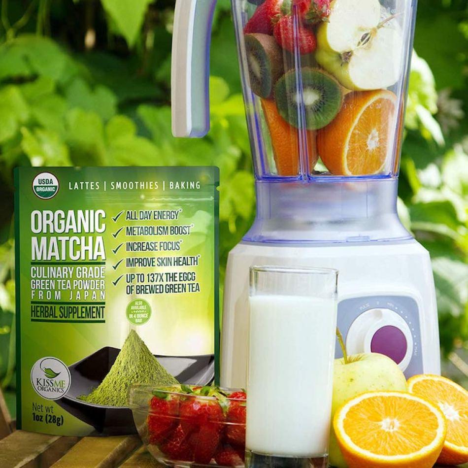 Kiss Me Organics Organic Matcha Green Tea Powder by a blender with fruit in it