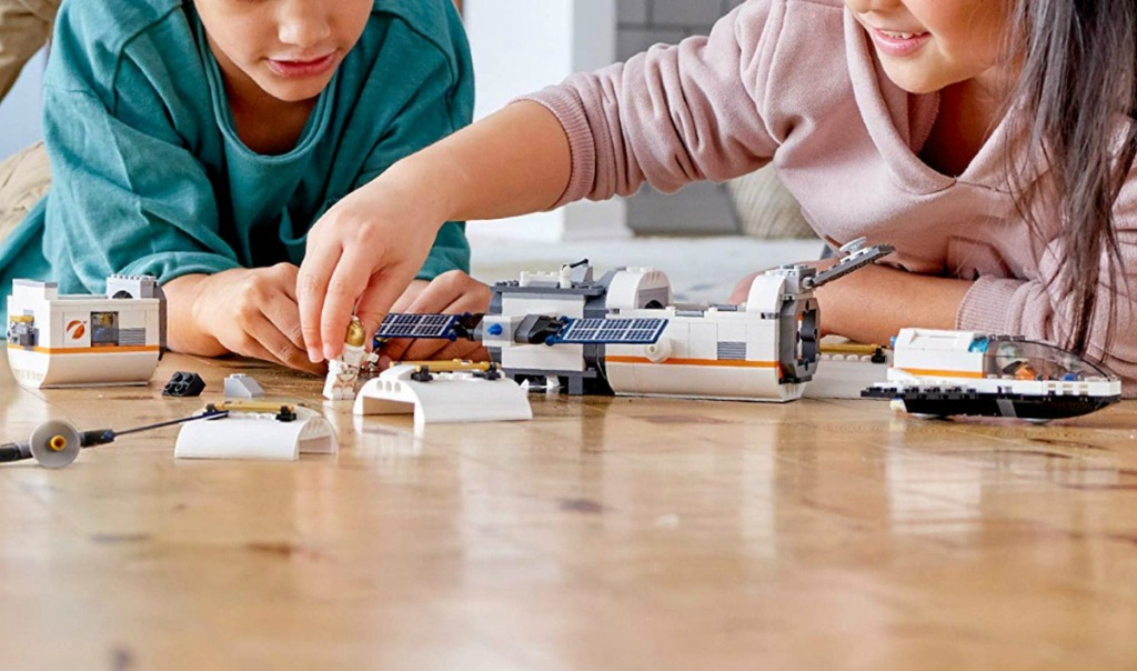 Two kids playing with the LEGO City Space Port Lunar Space Station Set