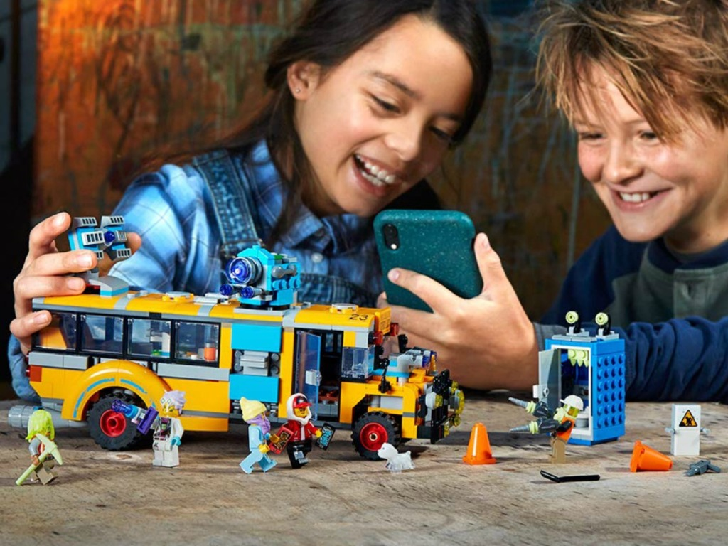 Boy & girl playing with a LEGO Hidden Side Bus set with a phone