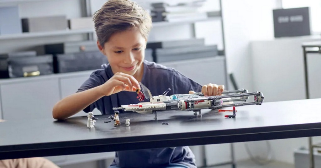 Boy playing with LEGO Star Wars Resistance Y-Wing Starfighter