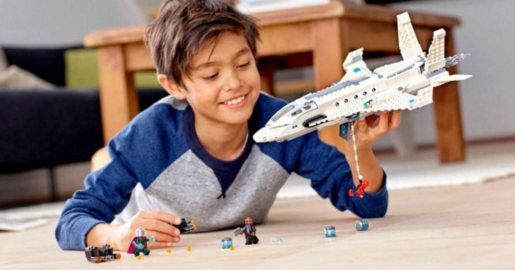boy playing with LEGO Marvel Stark Jet set