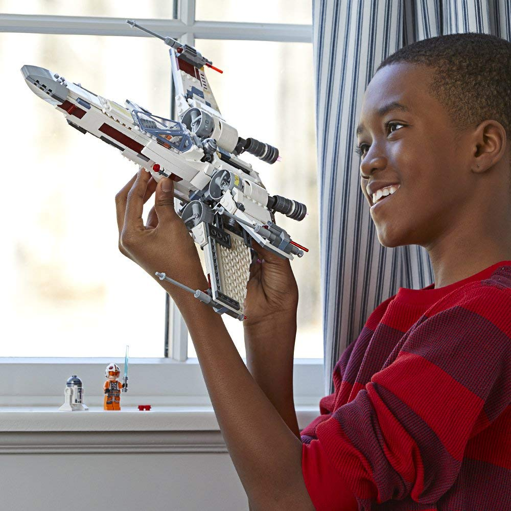 boy playing with LEGO X-wing