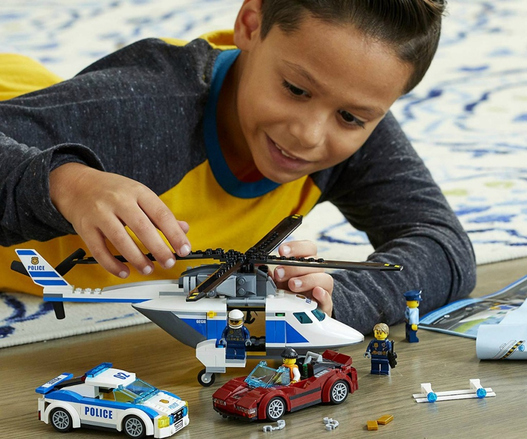 boy playing with a LEGO city set on the floor