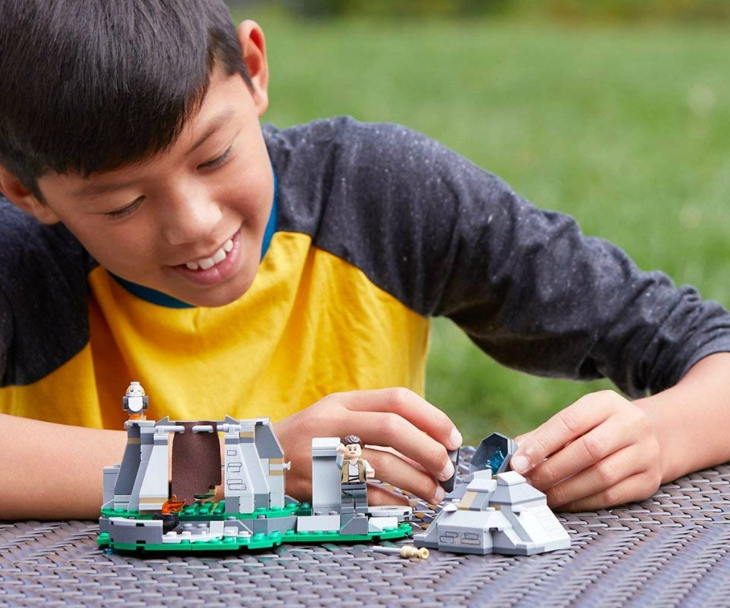 boy playing with a LEGO star wars set outside