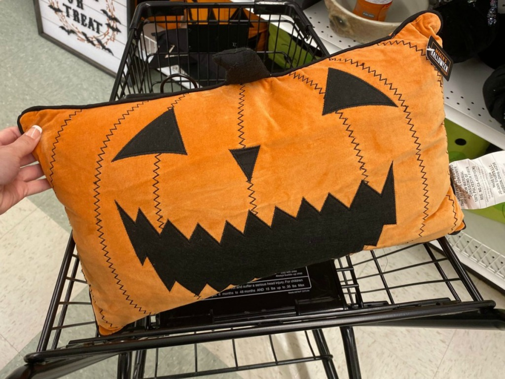 Halloween Jack-O-Lantern themed throw pillow in hand, in shopping cart, in-store